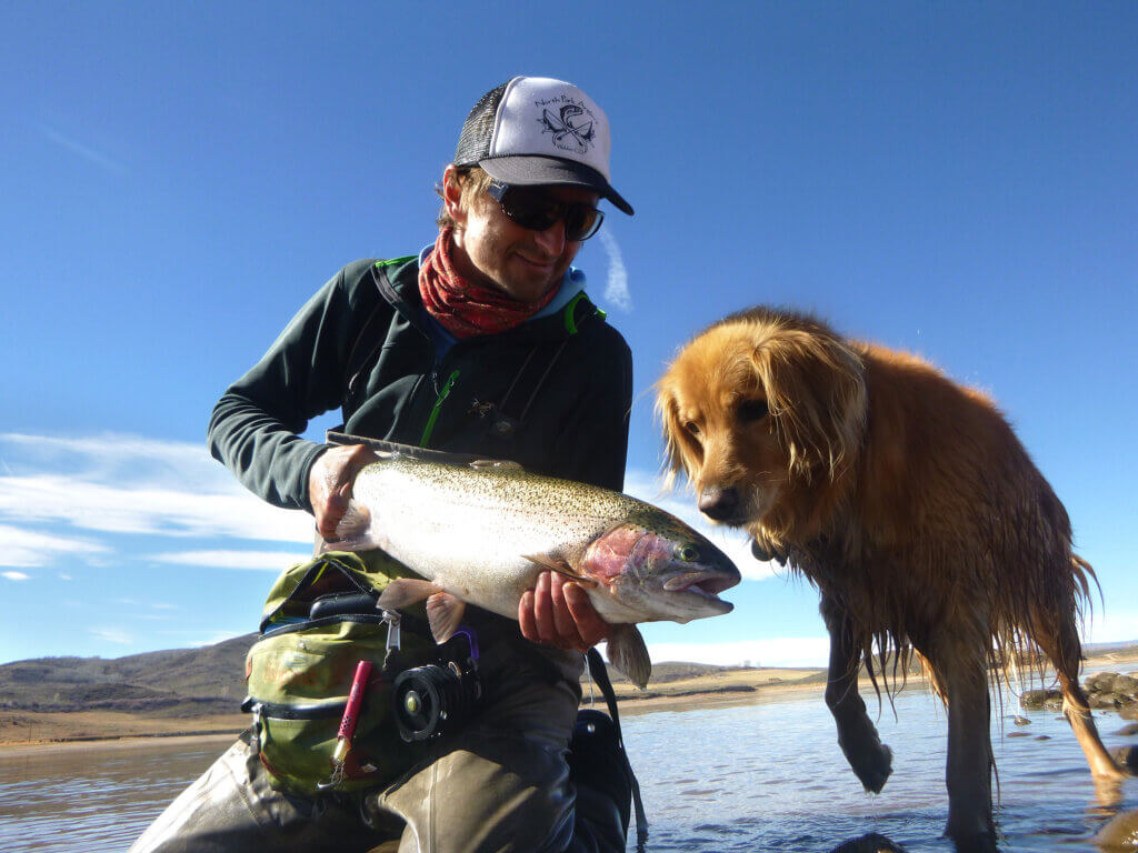Jackson Renner, ski tech and owner of Gore Range Sports and his dog catch a fish while fly-fishing.