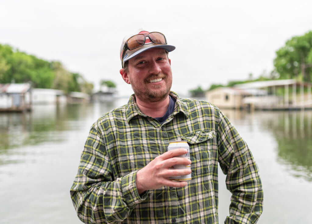 LD Zimmerman, Ski Tech and Bartender at Gore Range Sports drinking a beer by the river